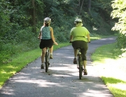 2 people riding on a trail with bicycles and wearing helmets to keep from getting a Traumatic Brain Injury